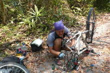Kybi repairing bike in the jungle