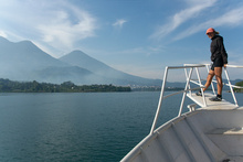 Dasa on the ferry with volcanoes in the background